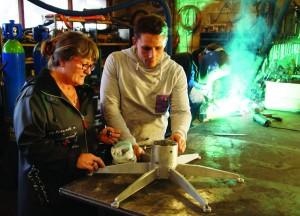 Mor Helle Bjeldbak og sønnen Emil med den ulakerede prototype i maskinværkstedet, hvor juletræsfoden er udviklet. Det er John, der svejser løs på i baggrunden.