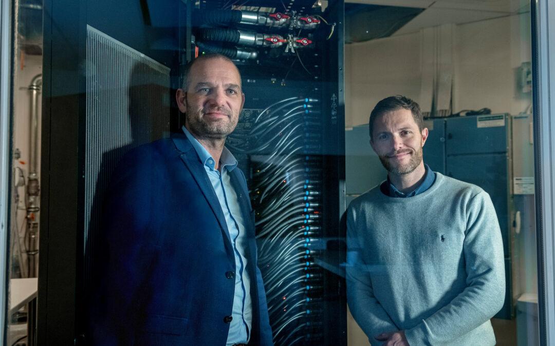 """Aseteks CEO André Sloth Eriksen (t.v.) og forsyningschef Jesper Møller Larsen fra Aalborgs fjernvarmenet (Aalborg Forsyning) i Aseteks testdatacenter, der netop er nomineret til Dansk Fjernvarmes """"Fjernvarmeprisen 2021""""."""